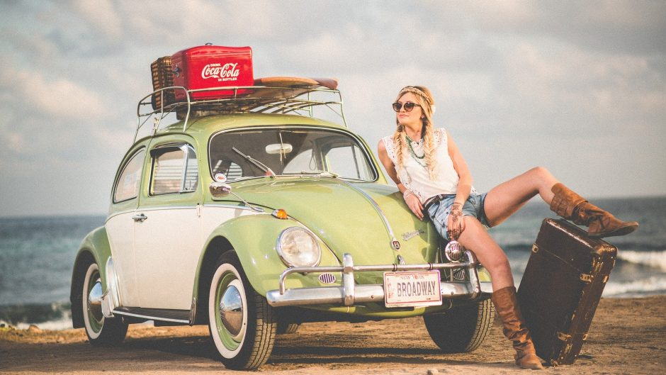 Stylish woman next to car on the beach